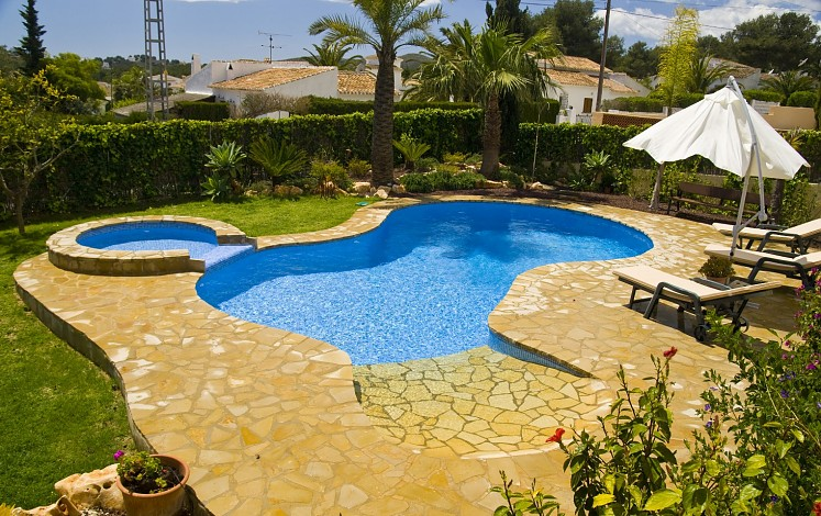 Irregular shaped pool and terrace with rustic stone